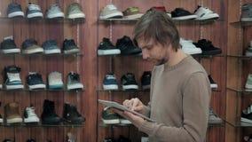 Negócio de Running Online Shoe do homem de negócios com a tabuleta de Digitas, estando na loja extrema da sapatilha vídeos de arquivo