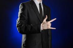 Negócio e a apresentação do tema: homem em um terno preto que mostra gestos de mão em uma obscuridade - fundo azul no estúdio iso Imagens de Stock Royalty Free