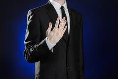 Negócio e a apresentação do tema: homem em um terno preto que mostra gestos de mão em uma obscuridade - fundo azul no estúdio iso Imagem de Stock Royalty Free