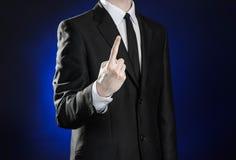 Negócio e a apresentação do tema: homem em um terno preto que mostra gestos de mão em uma obscuridade - fundo azul no estúdio iso Foto de Stock Royalty Free