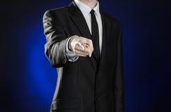 Negócio e a apresentação do tema: homem em um terno preto que mostra gestos de mão em uma obscuridade - fundo azul no estúdio iso Fotos de Stock Royalty Free