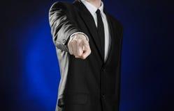 Negócio e a apresentação do tema: homem em um terno preto que mostra gestos de mão em uma obscuridade - fundo azul no estúdio iso Imagem de Stock