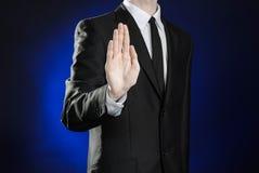 Negócio e a apresentação do tema: homem em um terno preto que mostra gestos de mão em uma obscuridade - fundo azul no estúdio iso Fotografia de Stock Royalty Free