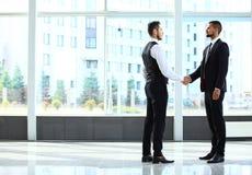 Negócio e conceito do escritório - dois homens de negócios que agitam as mãos fotografia de stock royalty free