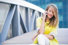 Negócio e conceito dos povos - mulher de negócios de sorriso nova que chama o smartphone sobre o prédio de escritórios Imagem de Stock