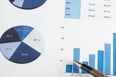 Negócio e finança dos gráficos com apontar da pena fotografia de stock