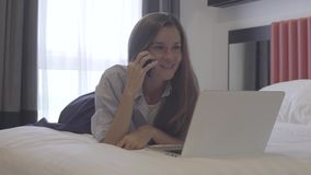 Negócio em linha A mulher fala no telefone ao trabalhar no portátil, mentira na cama vídeos de arquivo
