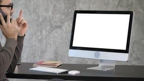 Negócio, fim do prazo e conceito da tecnologia - homem com computador que chama o smartphone e que aponta ao monitor branco imagem de stock