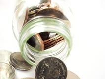 Negócio financeiro, moedas de derramamento, dinheiro do baht tailandês no vidro, isolado no fundo branco Foto de Stock Royalty Free