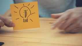 Negócio, mercado, planeamento e conceito dos povos - close-up da mão de uma mulher com um marcador que tira uma lâmpada em um ama vídeos de arquivo
