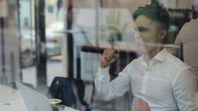 Negócio novo feliz que senta-se em uma tabela em um funcionamento do café em um portátil Vencedor que olha o portátil que mostra  video estoque