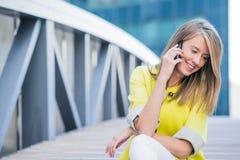 Negócio, tecnologia e conceito dos povos - mulher de negócios de sorriso com smartphone que fala sobre o prédio de escritórios Fotografia de Stock Royalty Free