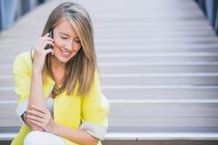 Negócio, tecnologia e conceito dos povos - mulher de negócios de sorriso com smartphone que fala sobre o prédio de escritórios Fotos de Stock