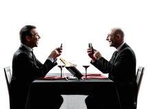 Negócio usando silhuetas do jantar dos smartphones Foto de Stock