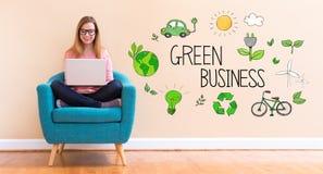 Negócio verde com a jovem mulher que usa seu portátil fotografia de stock