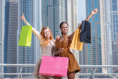 negócios Duas amigas bonitas nos vestidos que guardam a compra Foto de Stock