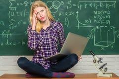 Negatieve gelaatsuitdrukking Vrouw freelancer met goede stemming die laptop computer met behulp van Vermoeide student Student met royalty-vrije stock afbeeldingen