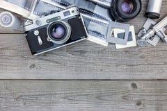 Negativa filmer, linser och retro kamera på trätabellbackgrou Fotografering för Bildbyråer