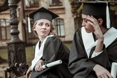 Negative delighted girls looking at each other. Want to study. Attractive leaver wearing graduation uniform while waiting for speech royalty free stock photo