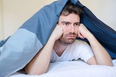 Negative emotion man lying in bed in the morning. Thoughtful and sad man face expression lying in the bed Stock Photo