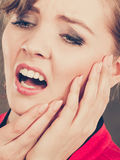 Negative emotion. Woman having tooth ache. Stress and pain. Face of young painful woman. Female feeling tooth pain ache. Girl touching her mouth teeth by hand royalty free stock images