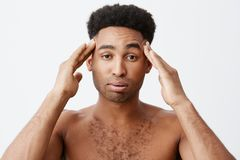 Negative emotions. Man having headache after partying all night. Close up of young dark-skinned male with afro hairstyle. Without clothes massaging head with Stock Image