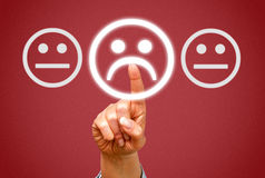 Negative feedback. A finger pressing frowning face icon, negative feedback and frustration and problems concept image royalty free stock images