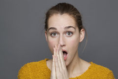 Negative feelings concept for embarrassed 20s girl. Negative feelings concept - embarrassed beautiful 20s girl expressing stunning mistake with body language and Royalty Free Stock Photo