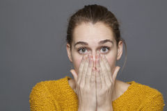 Negative feelings concept for shocked beautiful girl. Negative feelings concept - shocked beautiful 20s girl covering her mouth and nose with hands for emotions Stock Image