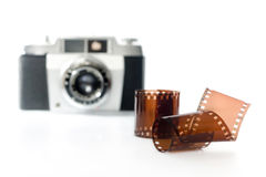 Negative film and camera. Film roll with old camera in background. selective focus. horizontal image Stock Images