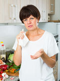 Negative mature woman. Housewife standing with napkin at her kitchen indoors Stock Photography