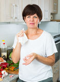 Negative mature woman. Housewife standing with napkin at her kitchen indoors Stock Photos