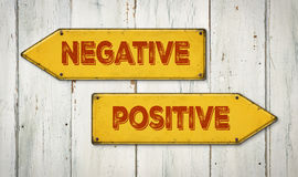 Negative or Positive. Direction signs on a wooden wall - Negative or Positive Royalty Free Stock Photography