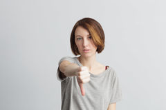 Negative review or opinion. Skinny girl shows displeasure thumb down Royalty Free Stock Image