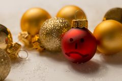Negative smiley on christmas ball - anti christmas. Negative smiley on red christmas ball - anti christmas Stock Image