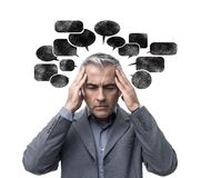 Negative thinking and stress. Pensive stressed man having negative thoughts and feeling confused, he is surrounded by dark speech bubbles stock images