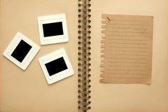 negativer Film auf braunem Buch mit braunem Notizblock Lizenzfreie Stockfotografie