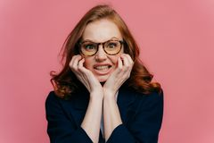 Negatywny czuciowy poj?cie Zawodzący rudzielec pomyślny bizneswoman zaciska zęby od drażnienia, utrzymanie ręki pod podbródkiem, obraz royalty free