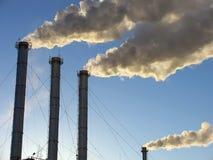 Negócio - skyline da cidade dos grampos Tubulação contra o céu que arrota o fumo Fotografia de Stock Royalty Free