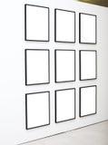 Negen lege frames op witte muurtentoonstelling Stock Foto's