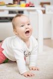 Negen maanden oud babymeisje spelen die op de vloer kruipen Stock Foto's