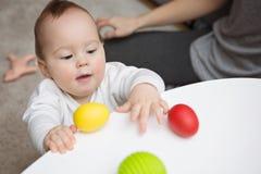 Negen van het babymaanden oud meisje dat kleurrijke stuk speelgoed eieren probeert te grijpen Royalty-vrije Stock Afbeelding