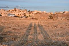 Negev öken, Arar bosättning, tre mänskliga skuggor på sanden på solnedgången Royaltyfria Foton