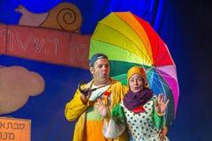 Negev, μπύρα-Sheva, Ισραήλ - δράστης θεάτρων ηθοποιών και των παιδιών στα εβραϊκά στη σκηνή με μια μεγάλη φωτεινή ομπρέλα στοκ εικόνες με δικαίωμα ελεύθερης χρήσης