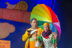 Negev, Beer-Sheva, Israel - Actress and children's theater actor in Hebrew on stage with a big bright umbrella. October 2015, youth Palace in Beer-Sheva city Royalty Free Stock Images