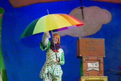 Negev, Beer-Sheva, Israel -Actress in Hebrew on stage with a big bright umbrella in polka dot jumpsuit. Children's theater actress in Hebrew on stage with a big Royalty Free Stock Photo