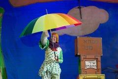Negev, cerveza-Sheva, Israel - actriz en hebreo en etapa con un paraguas brillante grande en mono del lunar Foto de archivo libre de regalías