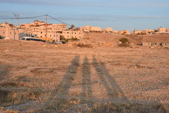Negev Desert, Arar settlement, three human shadows on the sand at sunset. Middle East Arara in the Negev, Israel May 11, Hina, Beersheba, Negev, Israel, 2016 Royalty Free Stock Photos