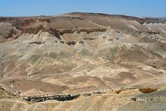 Negev desert of southern Israel in summer. Melange of brown, rocky, dusty mountains interrupted by wadis dry riverbeds, deep cra. Ters and roads royalty free stock photography