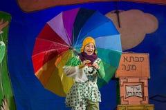 Negev öl-Sheva, Israel - barns teateraktris i hebré på etapp med ett stort ljust paraply i prickjumpsuit Arkivbilder
